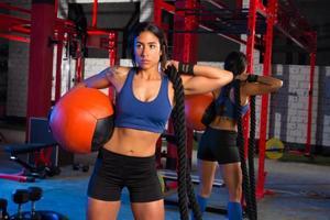 Gymnastikfrau mit gewichtetem Ball und Seil foto