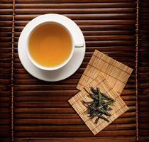 Tasse gebrühten grünen Tee mit Bambusuntersetzern foto