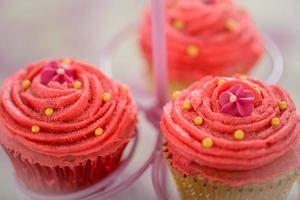 drei kitschrosa Bollywood-Cupcakes auf einem Tortenständer foto