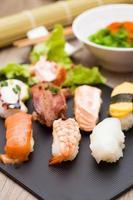 Sushi-Sortiment auf schwarzem Teller, Nahaufnahme foto
