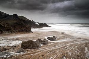 Leuchtturmlandschaft mit stürmischem Himmel über Meer mit Felsen foto