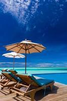 Liegestühle und Infinity-Pool über tropischer Lagune