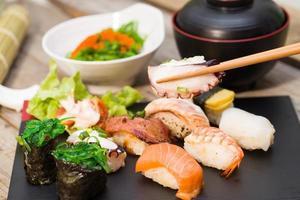 Sushi mit Stäbchen festklemmen foto