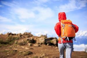 Wanderin der jungen Frau, die auf schönem Berggipfel wandert