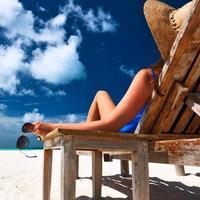 Frau am Strand hält Sonnenbrille foto