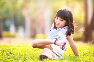 kleines asiatisches Mädchen auf Gras im Garten