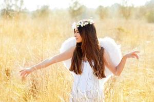 Engelsmädchen im goldenen Feld mit federweißen Flügeln foto