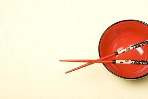 rote leere Schüssel im asiatischen Stil mit Stäbchen auf Seidenbackboden. foto