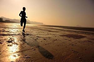 junge Fitnessfrau, die am Sonnenaufgangstrand läuft
