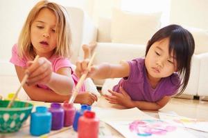 zwei Mädchen, die auf dem Boden liegen und Bild zu Hause malen foto