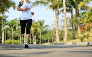 Läuferin, die auf tropischem Parkweg läuft foto
