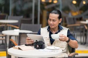 Mann mit Kaffee und digitalem Tablet foto