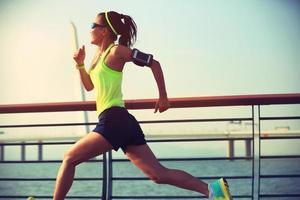 junger Fitnessfrauenläufer, der am Meer läuft foto