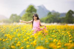 kleines asiatisches Mädchen in Blumenfeldern foto