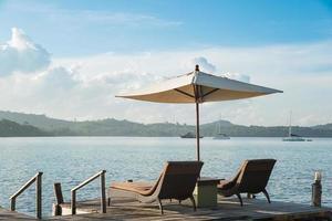 zwei Stühle und Regenschirm auf Holzschreibtisch gegen blauen Himmel