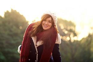 schönes Mädchen in der Winterkleidung, die mit Sonnenuntergang lächelt foto