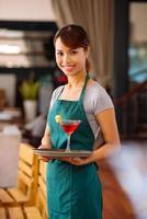 Kellnerin mit einem Cocktail foto
