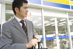 Mann, der Energiegetränk vor dem Supermarkt hält foto