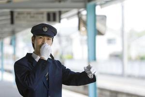 Stationsmitarbeiter machen Ankündigung auf dem Bahnsteig foto