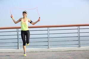 junge Fitnessfrau springendes Seil am Meer