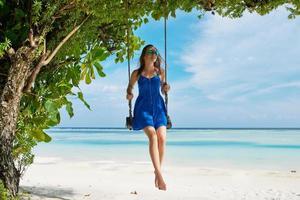 Frau im blauen Kleid schwingt am Strand