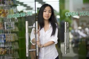 süße asiatische Frau offene Tür im Buchladen foto