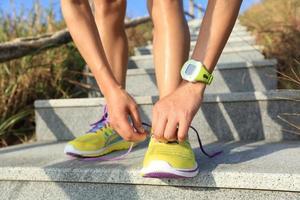 junge Frau Läufer, die Schnürsenkel auf Steinweg binden foto