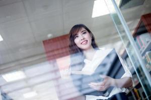 asiatische schöne Studentin, die Buch im Bibliotheksporträt hält foto