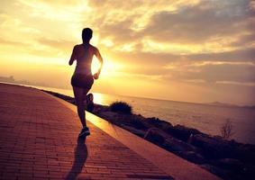 asiatische Frau des gesunden Lebensstils, die am Sonnenaufgang am Meer läuft foto