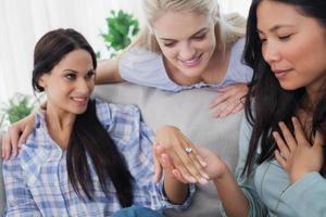 lächelnde Freunde, die brünetten Verlobungsring bewundern