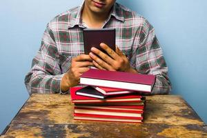 junger Mann, der auf einem digitalen Leser liest foto
