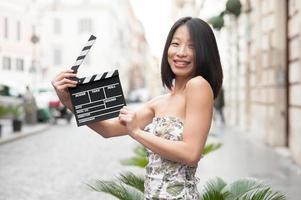 junge asiatische Frau lächelnd zeigt Klappentafel