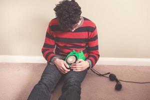 trauriger Mann auf dem Boden mit Telefon foto