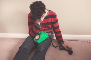 trauriger Mann, der schlechte Nachrichten am Telefon erhält foto