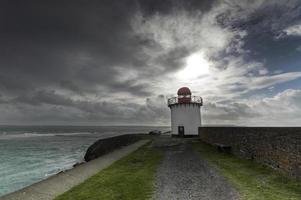 Leuchtturm unter stürmischem Himmel foto