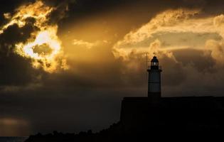 schöner lebendiger Sonnenaufgangshimmel über ruhigem Wasserozean mit Leuchtturm