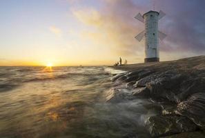 Sonnenuntergang an der Küste, Leuchtturm Windmühle in Swinoujscie, Polen. foto