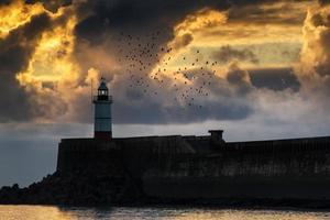 schöner lebendiger Sonnenaufgangshimmel über ruhigem Ozean mit Leuchtturm