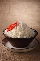 Reisschüssel mit frischen Chilischoten auf braunem rustikalem Hintergrund,
