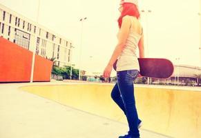 Skateboarderin, die am Skatepark geht foto