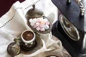 türkischer Kaffee mit Genuss und traditionellem Servierset, Vintage-Uhr foto