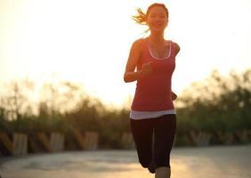 Läuferin, die morgens Sonnenaufgang im Freien läuft foto