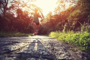 Läuferathlet, der auf Waldweg läuft.