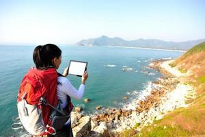 Wanderfrau verwenden Tablet PC am Meer