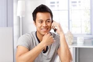 junger Mann auf dem Handy lächelnd foto