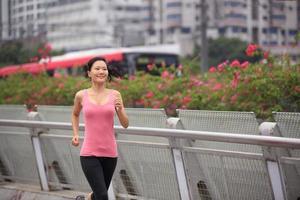 gesunde asiatische Frau, die in der modernen Stadt läuft foto
