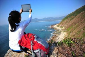 Wanderfrau verwenden digitale Tablette am Meer