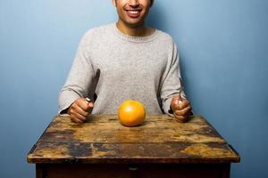 gesunder junger Mann, der eine Grapefruit zum Abendessen hat foto
