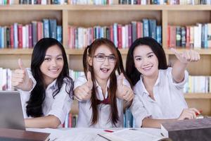 glückliche Lernende zeigen Handbewegung in der Bibliothek foto