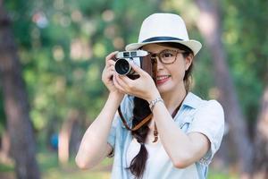 schönes asiatisches Mädchen lächelnd mit Retro-Kamera, die Sie fotografiert
